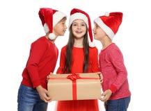 Bambini svegli in cappelli di Santa con il contenitore di regalo di Natale su fondo bianco Fotografie Stock