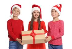 Bambini svegli in cappelli di Santa con il contenitore di regalo di Natale su fondo bianco Immagine Stock