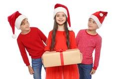 Bambini svegli in cappelli di Santa con il contenitore di regalo di Natale su fondo bianco Fotografia Stock Libera da Diritti