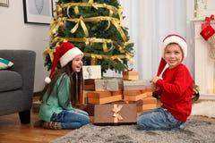 Bambini svegli in cappelli di Santa con regalo di Natale immagine stock libera da diritti