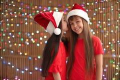 Bambini svegli in cappelli di Santa sul fondo vago delle luci Celebrazione di natale Fotografie Stock Libere da Diritti
