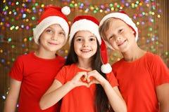 Bambini svegli in cappelli di Santa sul fondo vago delle luci Celebrazione di natale Immagini Stock