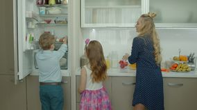 Bambini svegli che aiutano madre a produrre prima colazione a casa video d archivio