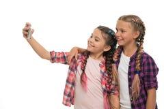 Bambini svegli delle ragazze piccoli che sorridono per telefonare schermo Gradiscono prendere il selfie per le reti sociali Probl fotografia stock libera da diritti