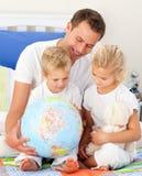 Bambini svegli e loro il padre che esaminano un glob Fotografie Stock