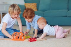 Bambini svegli, fratelli germani che giocano insieme i giocattoli sul tappeto a casa fotografie stock libere da diritti