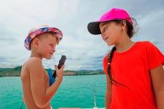 Bambini svegli su un viaggio della barca Il ragazzo sta giocando una chitarra del giocattolo e canta Fotografie Stock