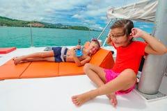 Bambini svegli su un viaggio della barca Il ragazzo sta giocando una chitarra del giocattolo per il suo è Fotografia Stock Libera da Diritti