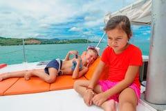 Bambini svegli su un viaggio della barca Il ragazzo sta giocando una chitarra del giocattolo per il suo è Fotografia Stock