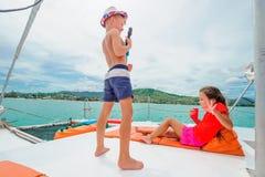 Bambini svegli su un viaggio della barca Il ragazzo sta giocando una chitarra del giocattolo per il suo è Immagini Stock Libere da Diritti