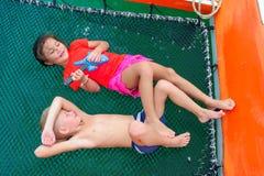 Bambini svegli su un viaggio della barca La ragazza sta giocando una chitarra del giocattolo per la sua f Immagini Stock