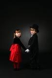 Bambini svegli in vestiti convenzionali che tengono le mani fotografia stock