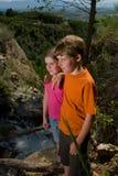 Bambini tramite un flusso della montagna fotografia stock libera da diritti