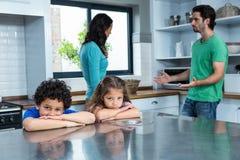Bambini tristi che ascoltano la discussione dei genitori Immagini Stock