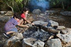 Bambini in un fuoco di accampamento immagine stock