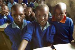 Bambini in uniformi blu alla scuola dietro lo scrittorio vicino al parco nazionale di Tsavo, Kenya, Africa Fotografia Stock
