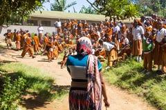 Bambini in uniformi che giocano nel cortyard della scuola primaria nella zona rurale vicino ad Arusha, Tanzania, Africa Fotografie Stock