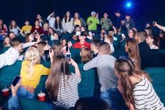 Bambini usciti nel corridoio del cinema che indicano sul ragazzo che guarda 3D-eyeglasses fotografia stock libera da diritti