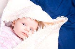 Bambino abbastanza sonnolento sotto una coperta Fotografia Stock
