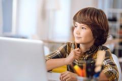 Bambino abile che impara le lezioni dovuto il computer Fotografie Stock
