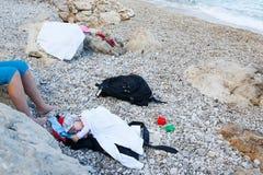 Bambino addormentato che si trova su una spiaggia pebbled Fotografie Stock Libere da Diritti