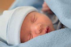 Bambino addormentato in coperta blu fotografia stock