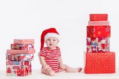 Bambino adorabile in cappuccio di Santa con le pile di scatole attuali intorno alla seduta sul pavimento. Isolato su fondo bianco Immagini Stock