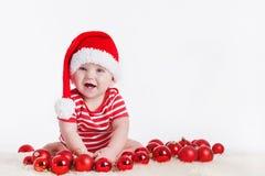 Bambino adorabile in cappuccio di Santa con le pile di scatole attuali intorno alla seduta sul pavimento. Isolato su fondo bianco Fotografie Stock
