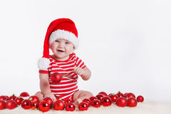 Bambino adorabile in cappuccio di Santa con le pile di scatole attuali intorno alla seduta sul pavimento. Isolato su fondo bianco Fotografia Stock Libera da Diritti
