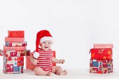Bambino adorabile in cappuccio di Santa con le pile di scatole attuali intorno alla seduta sul pavimento. Isolato su fondo bianco Immagine Stock