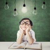 Bambino adorabile con il libro che cerca lampada Fotografia Stock Libera da Diritti