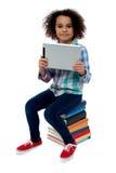Bambino adorabile con il pc della compressa che si siede sui libri Fotografie Stock Libere da Diritti