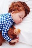 Bambino adorabile del bambino della testarossa che dorme con il giocattolo della peluche in flanella immagine stock libera da diritti