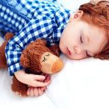 Bambino adorabile del bambino della testarossa che dorme con il giocattolo della peluche in pigiami della flanella fotografia stock