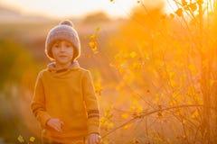 Bambino adorabile, divertendosi sul tramonto, facendo i fronti e Dan divertenti Fotografie Stock