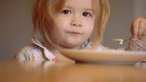 Bambino adorabile felice sorridente che mangia la poltiglia della frutta nella cucina Ragazzino che mangia prima colazione nella  video d archivio