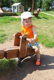 Bambino adorabile sull'altalena a bilico di estate Fotografie Stock Libere da Diritti