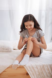 Bambino affascinante che mette fasciatura adesiva sul ginocchio a casa Fotografie Stock Libere da Diritti