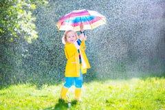 Bambino affascinante con l'ombrello che gioca nella pioggia Fotografia Stock
