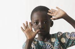 Bambino africano che protegge il suo fronte con le sue mani, isolate su wh fotografie stock
