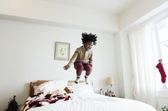 Bambino africano che si diverte che salta su un letto Immagine Stock