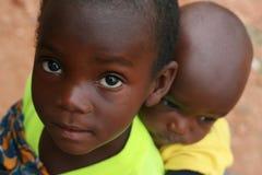 Bambino africano che trasporta piccolo modo dell'Africano del bambino Immagini Stock Libere da Diritti