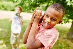 Bambino africano con il telefono del barattolo di latta immagini stock libere da diritti
