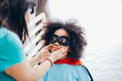 Bambino afroamericano che è sostenuto ed aiutato tramite la madre complementare per poche avventura e protezione fotografie stock libere da diritti