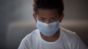 Bambino afroamericano nella maschera medica che guarda in camera con gli occhi tristi, epidemia fotografia stock