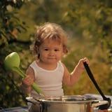 Bambino all'aperto ragazzo sorridente con capelli ricci biondi in biancheria intima bianca che tiene l'utensile nero e verde e co Immagine Stock