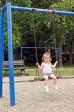 Bambino all'oscillazione del campo da giuoco Fotografia Stock Libera da Diritti