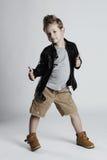 Bambino alla moda in cappotto di cuoio acconciatura del ragazzino bambino sorridente divertente fotografia stock libera da diritti