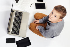 Bambino alla moda con i computer, compresse, telefoni, aggeggi intorno Immagini Stock