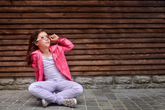 Bambino alla moda della bambina che porta un rivestimento rosa di autunno o di estate, jeans bianchi, occhiali da sole fotografia stock libera da diritti